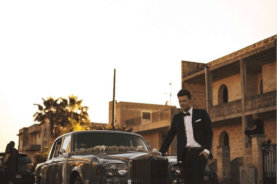 a groom standing in front of a limo